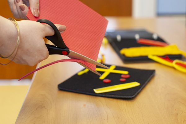 close up of hands cutting red and yellow craft materials