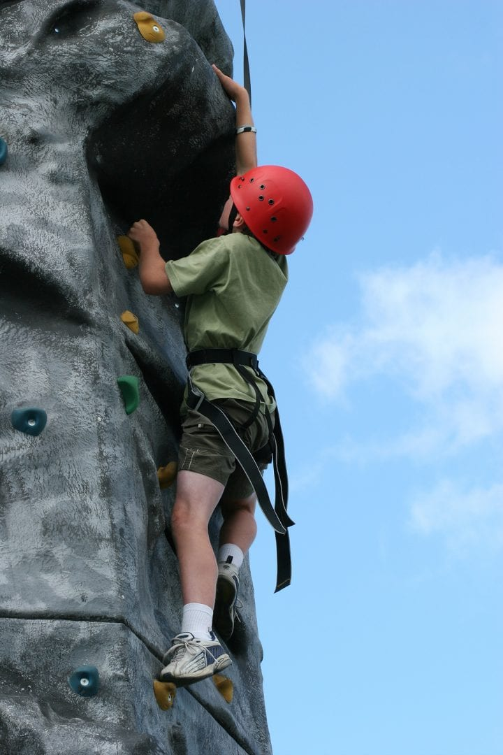 boy climbing on a training rock face
