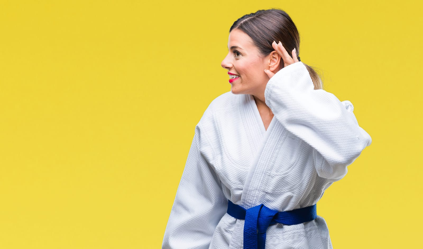 Woman wearing karate kimono uniform over isolated background smiling with hand over ear listening