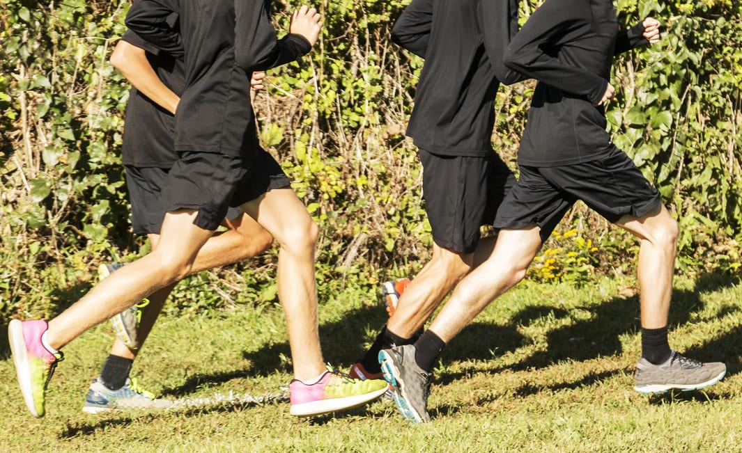 boys high school cross country team running in a group