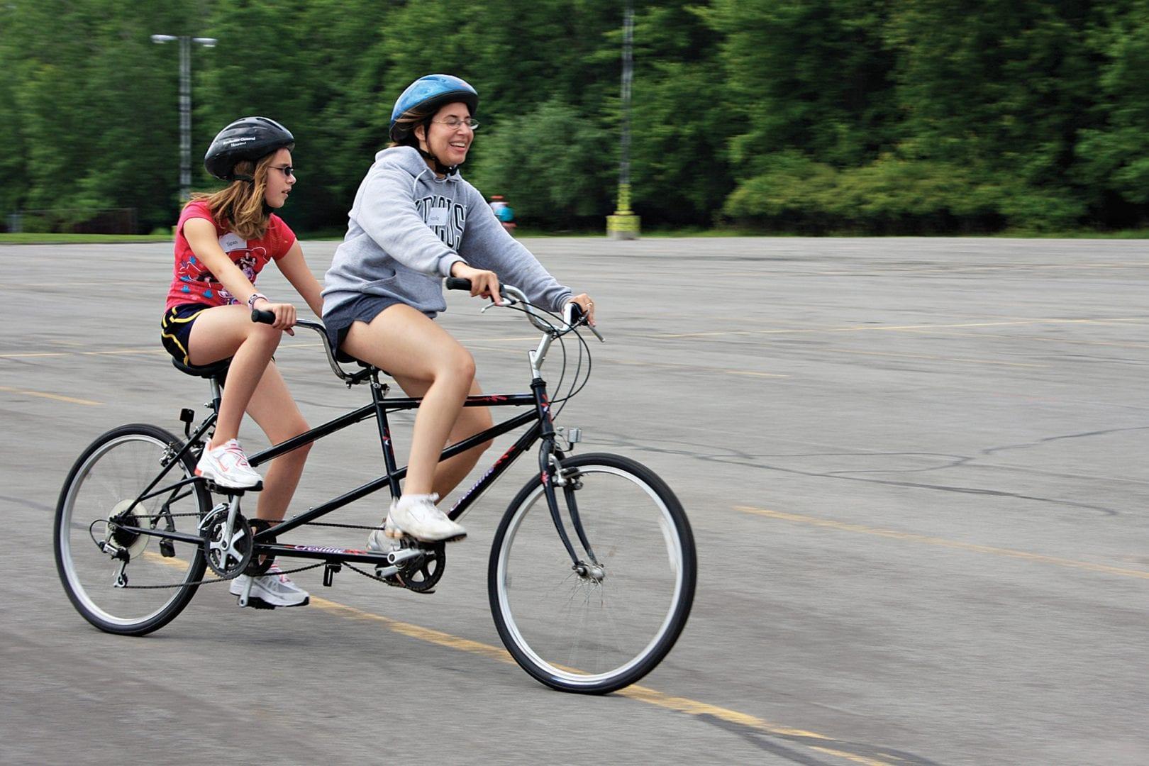 Two women riding a tandem bike