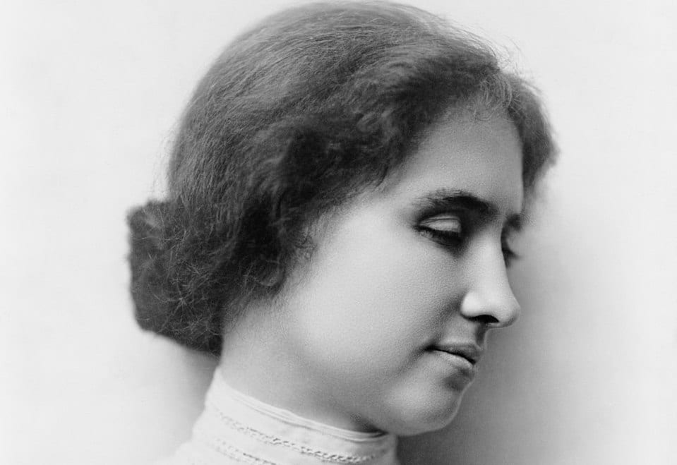 A black and white photo of Helen Keller with her head turned to the right