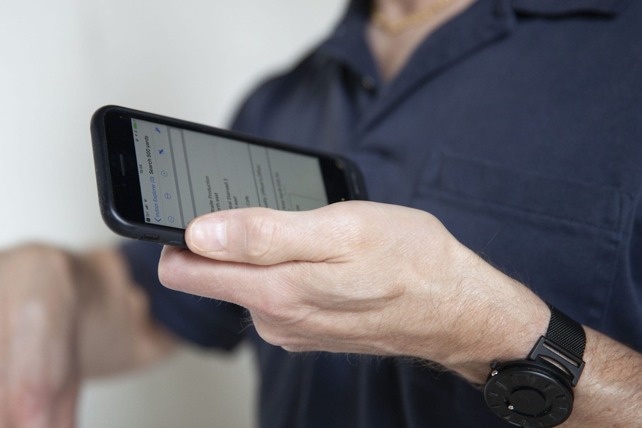A man's hand holding an iPhone which is displaying the Indoor Explorer search screen.