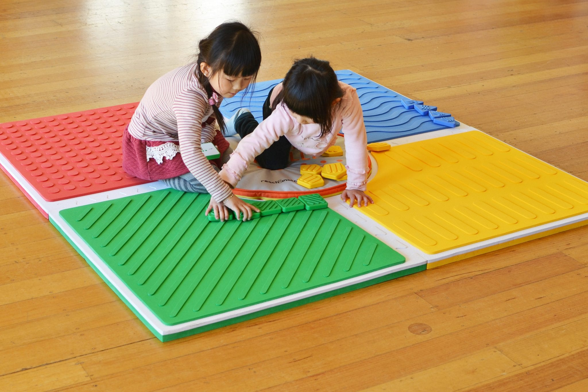 Two young girls playing on Reach & Match mat