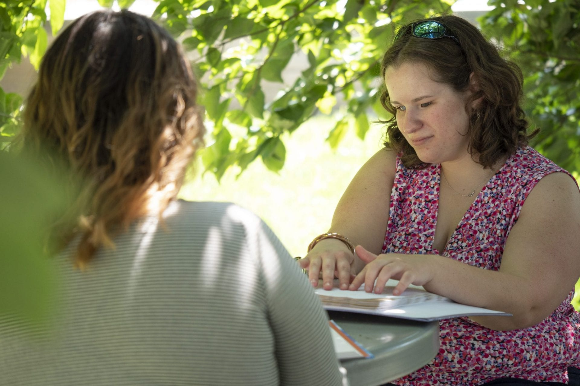 A student reads a braille textbook while sitting outside under a tree with a friend