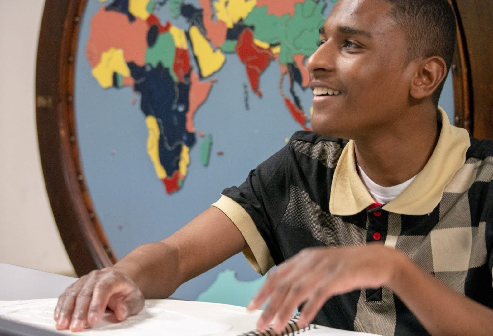 Teenage boy reading braille and smiling in front of a tactile map of the world