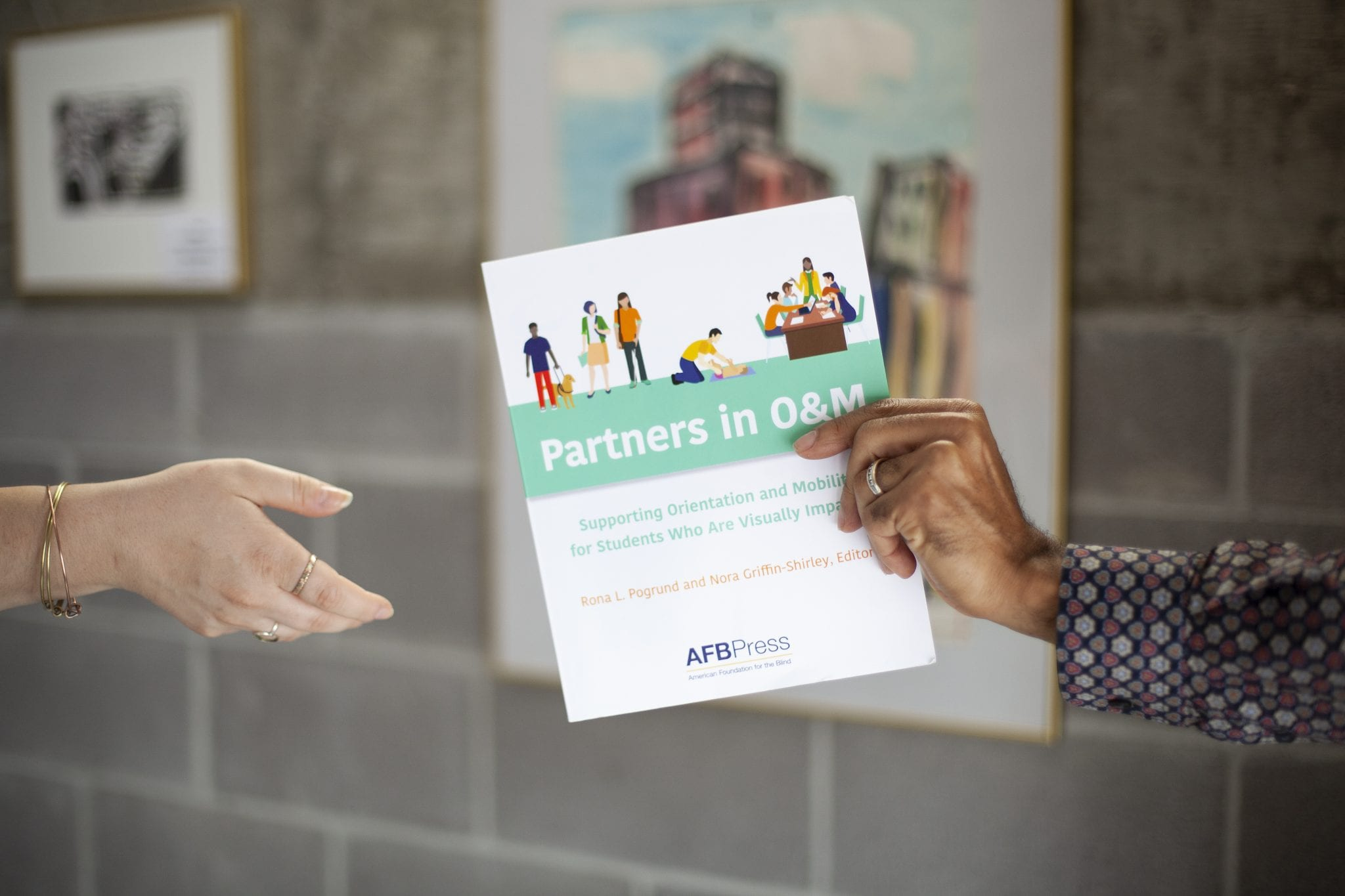 Two hands exchanging a card promoting AFB Press' Partners in O&M book