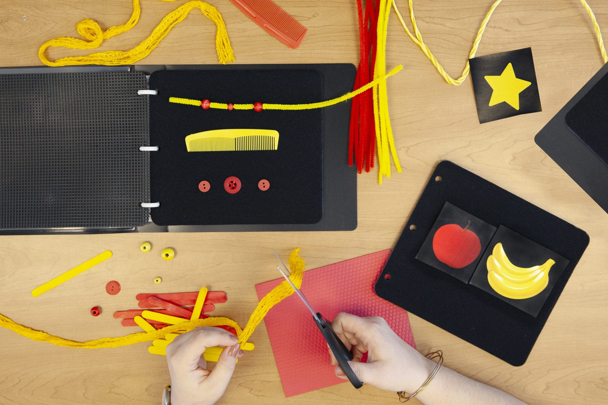 Close up of adult hands cutting red and yellow materials for the APH CVI Book Builder