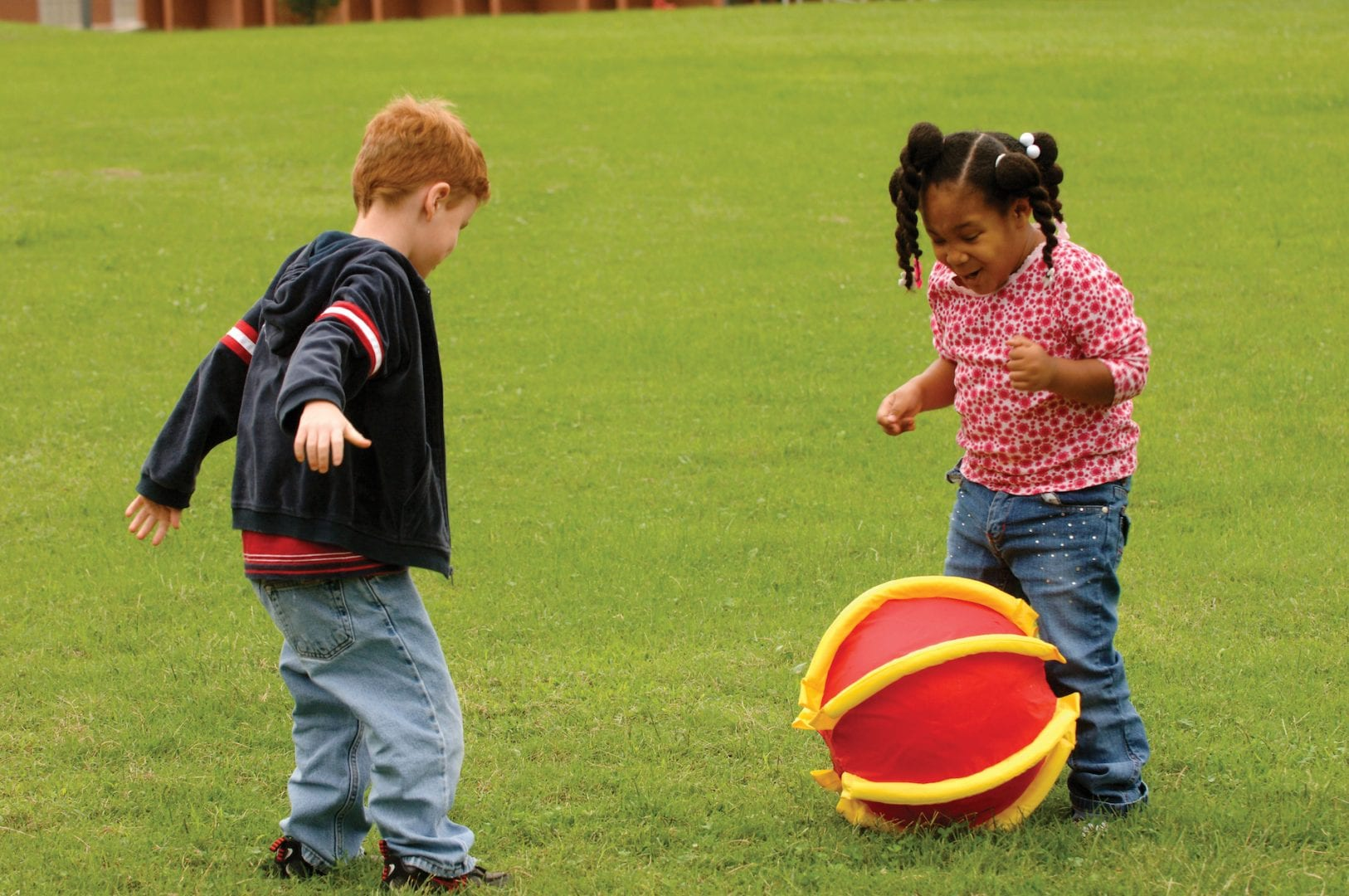 Young boy and girl playfully kicking a APH Rib-it Ball