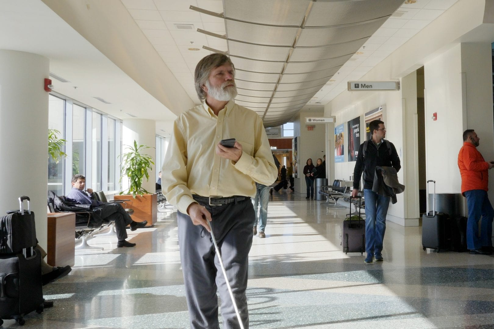 Man navigating through an airport with a white cane and cellphone