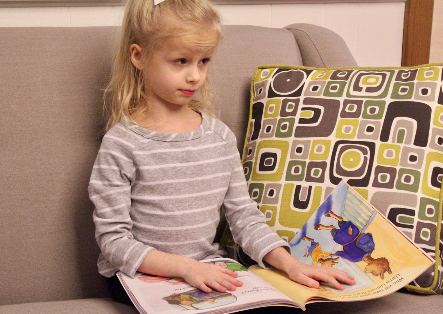 a young girl reading a braille tales book