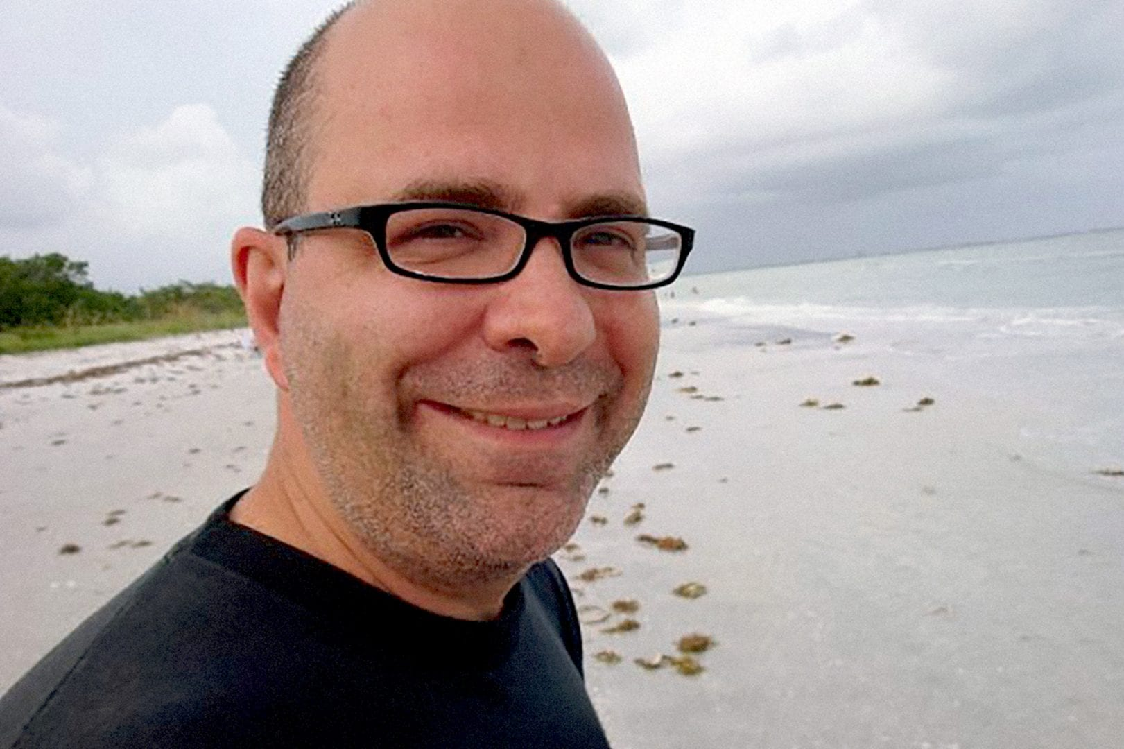 A close up photo of a man with glasses