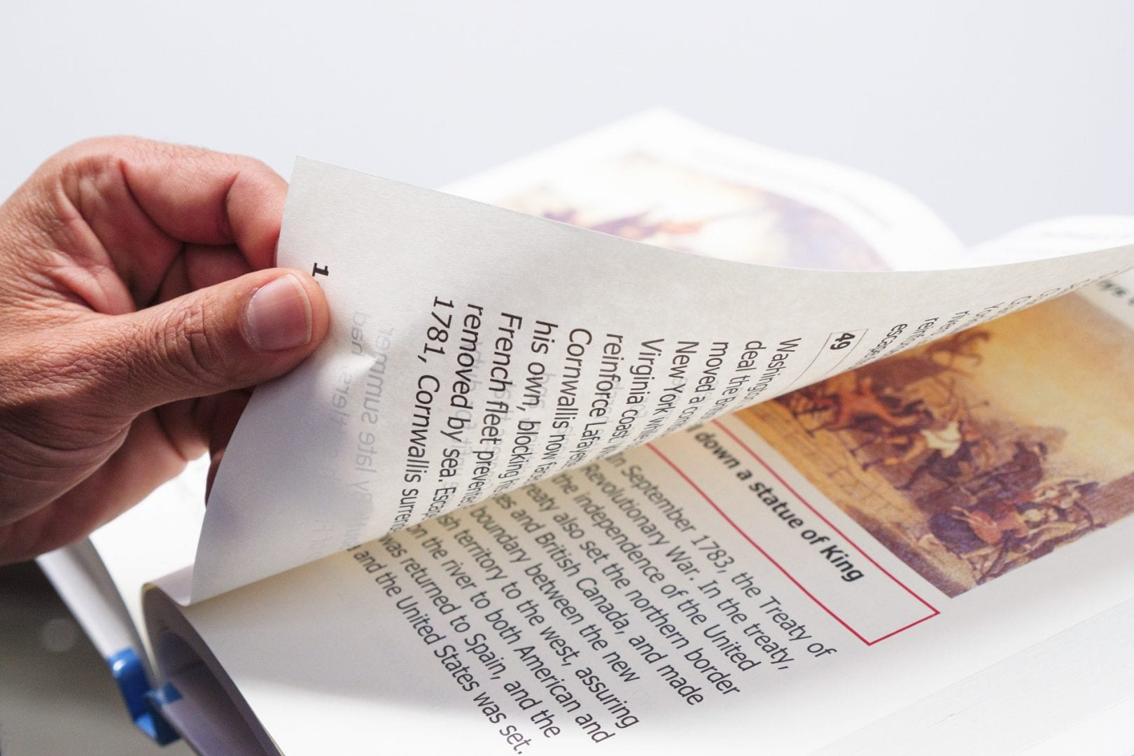 A hand turning a page of a book