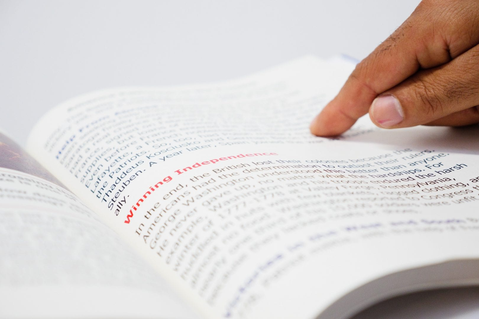 a hand tracking paragraphs on a book