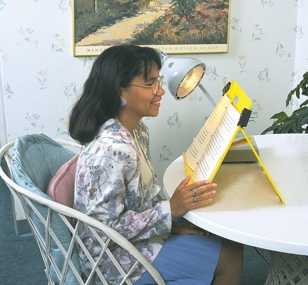 A woman sitting at a table using the GrandStand Portable Reading Easel