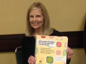 Dr. Catherine Nelson holding a copy of Child-guided Strategies: The Van Dijk Approach to Assessment