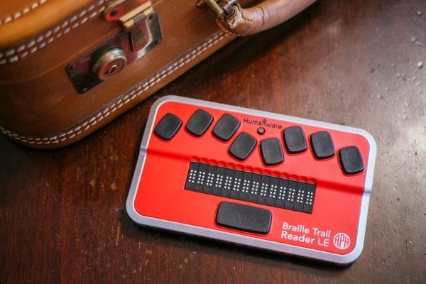Braille Trail Reader next to a suitcase