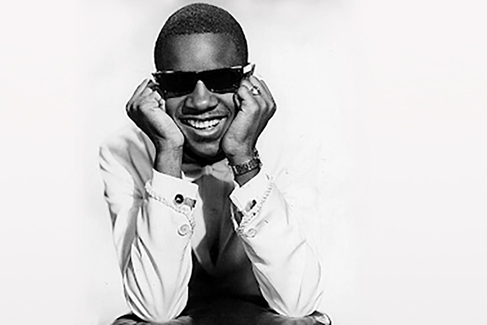 young Stevie Wonder with his head resting in his hands