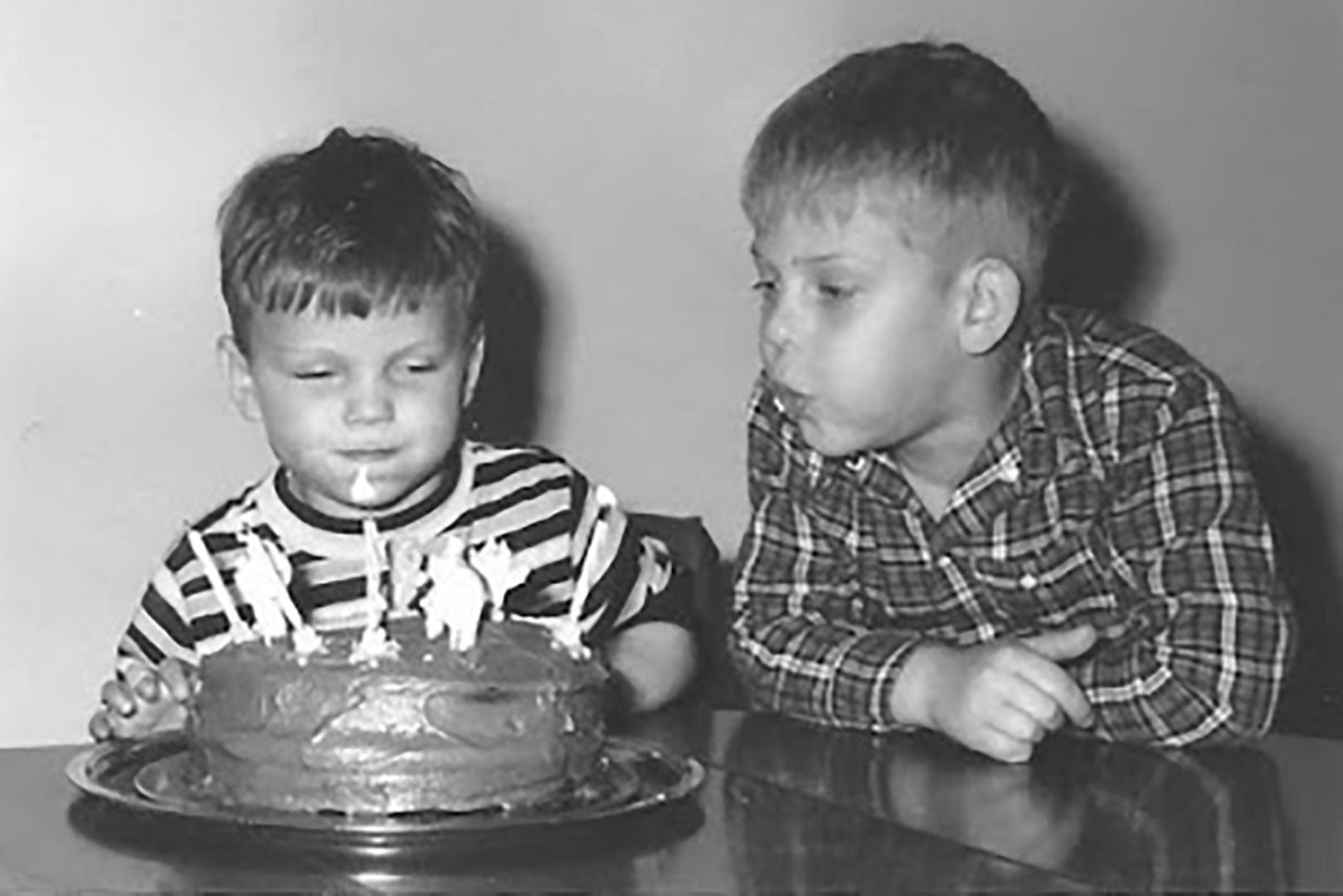young Dave blowing out birthday cake candles with help of is older brother