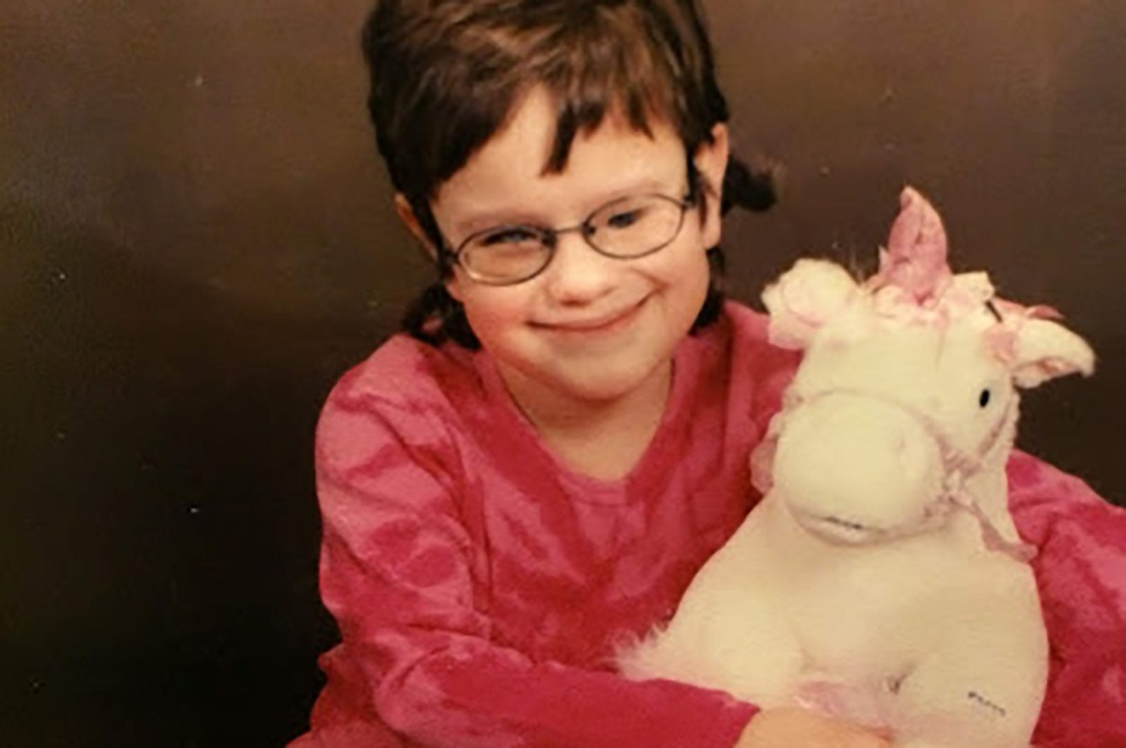 Young Jessica posing for a photo with a stuffed unicorn