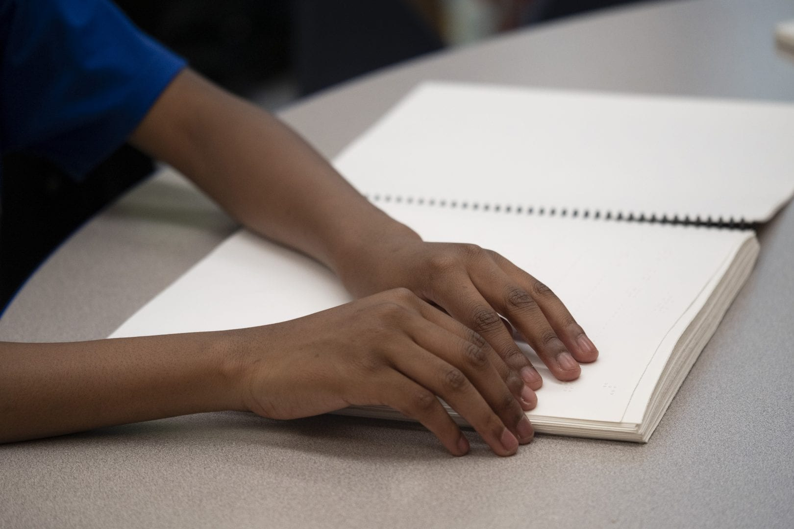 a students hands on a braille spiral bound book