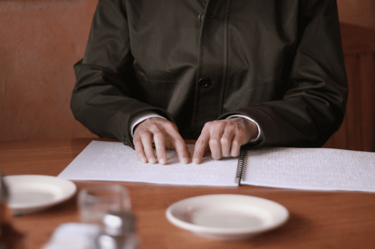 hands on a braille menu in a restaurant