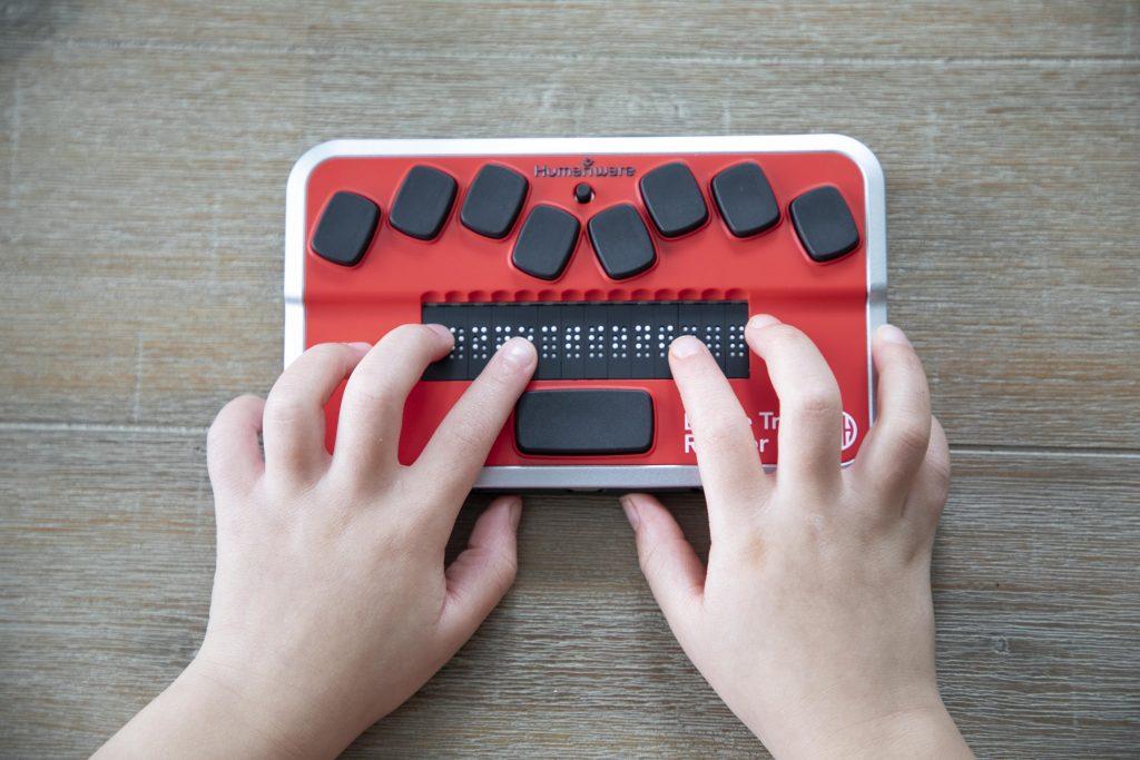 Kid's hands in braille trail reader