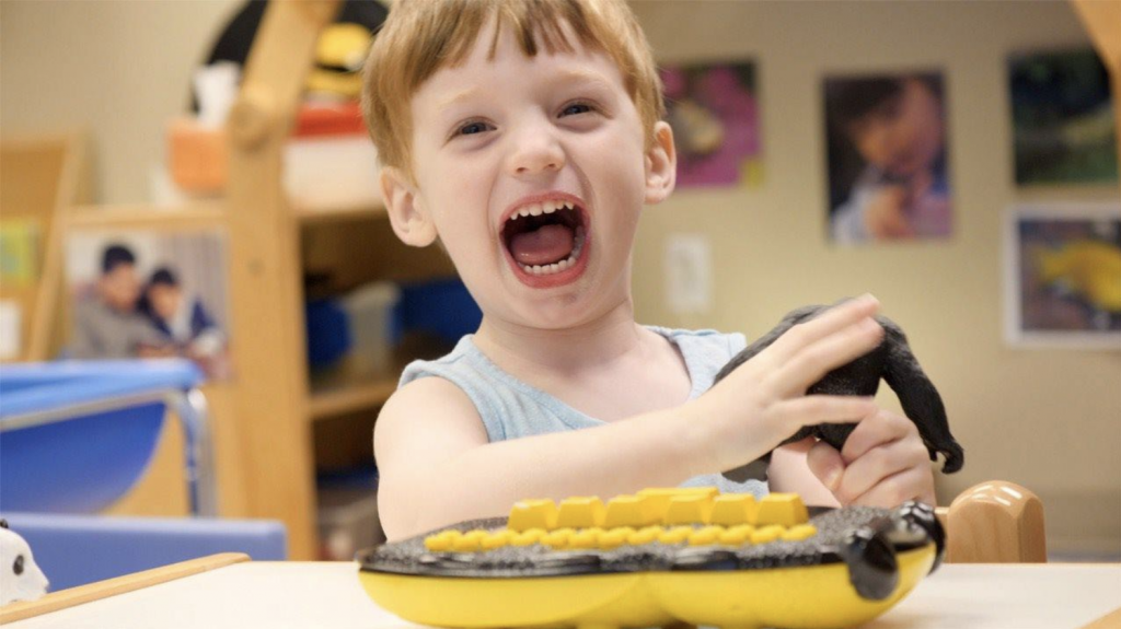 boy smiling with Braille Buzz