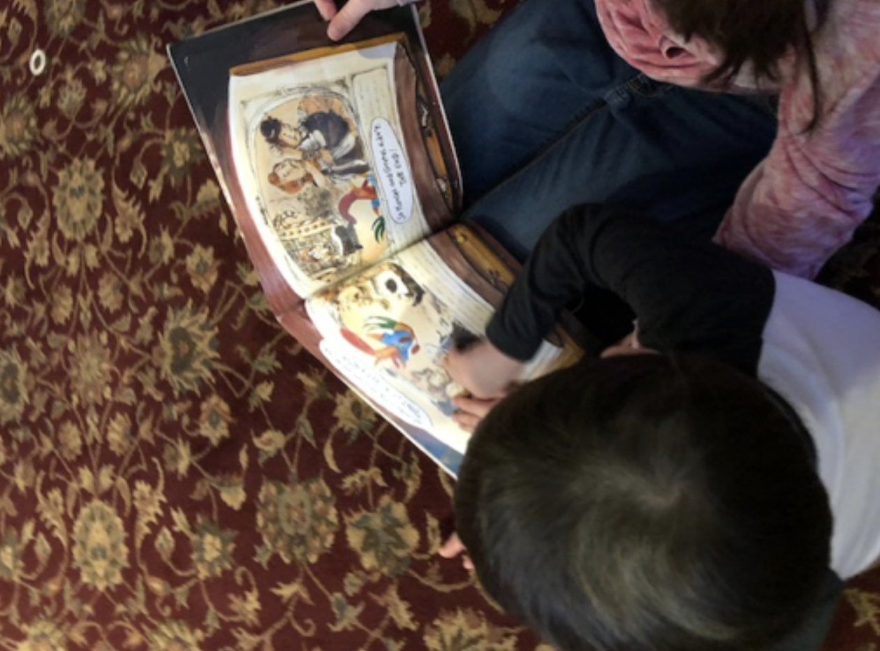 overhead shot of an older girl helping a younger boy read a braille story book