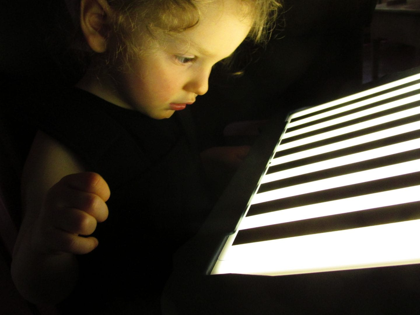 a child looking at a lightbox overlay in the dark