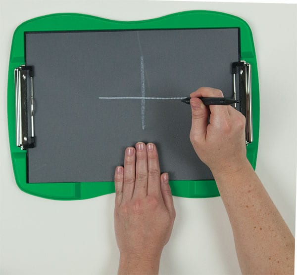 View of the TactileDoodle from above. A person's left hand steadies the board while the right hand has drawn two intersecting lines