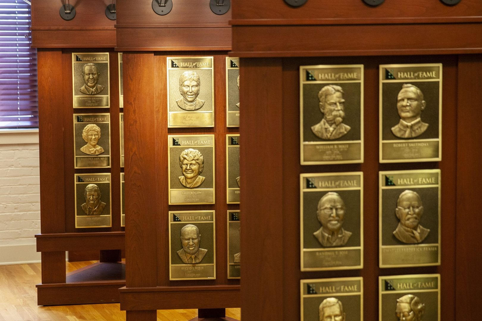 three wooden stands displaying bronze portrait plaques of hall of fame inductees