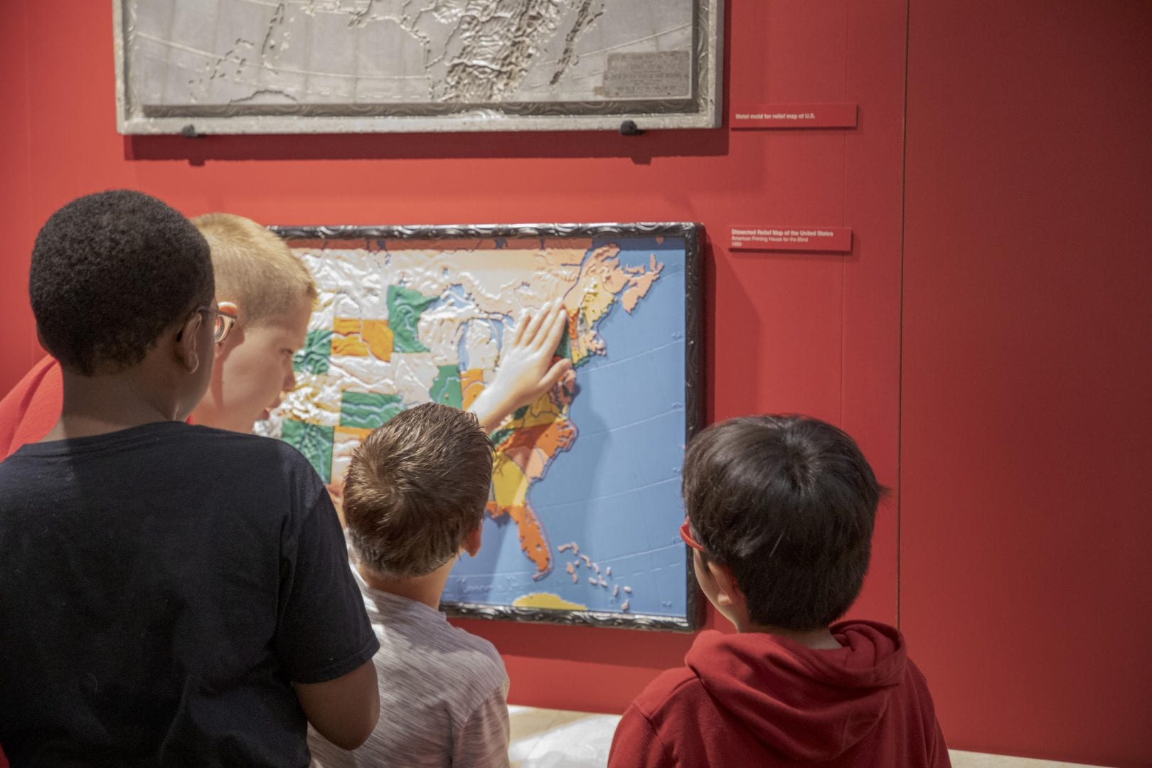kids looking at and feeling a tactile map of the US in the APH Museum