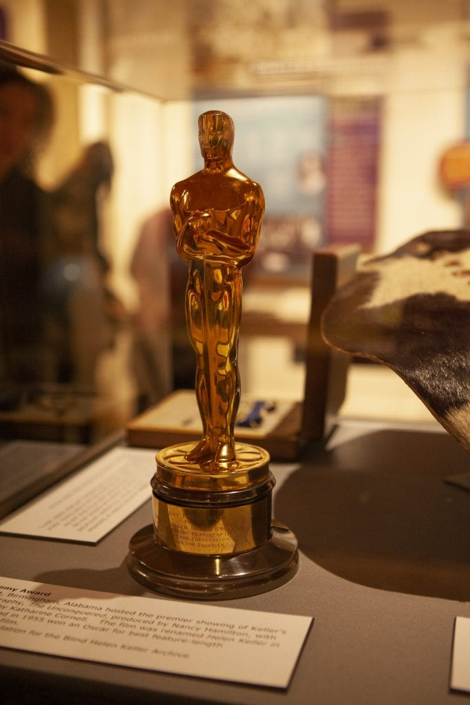 Helen Keller's academy award in a case in a museum. people out of focus in the distance