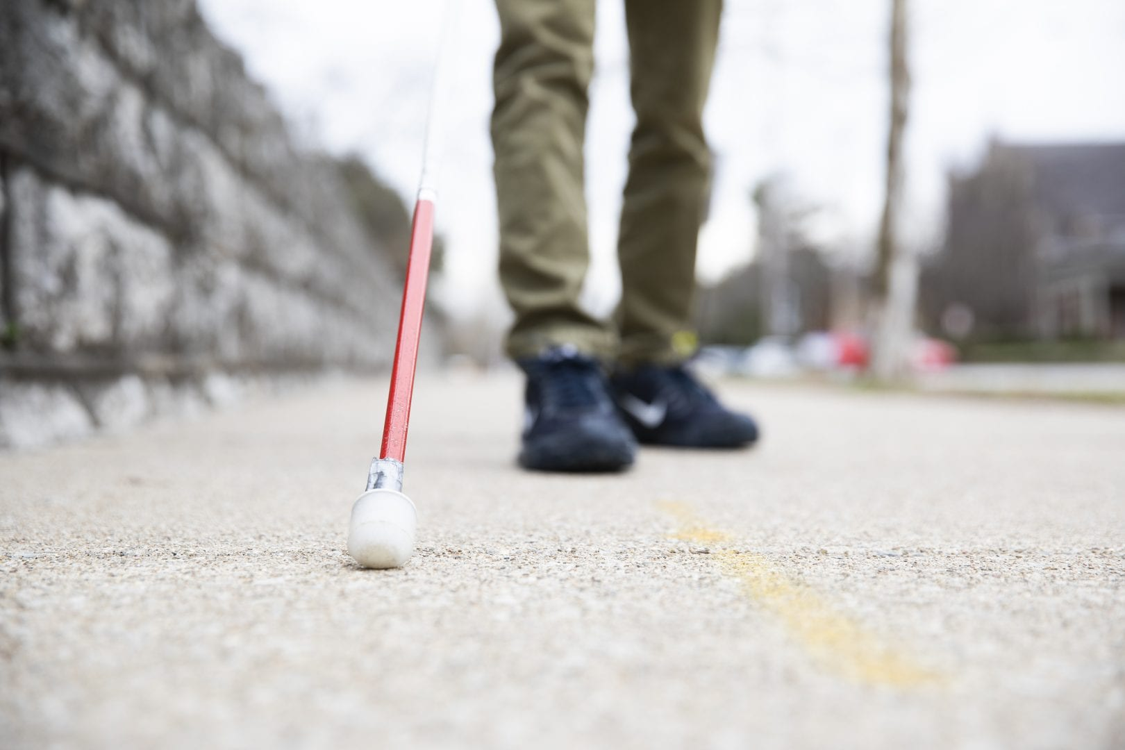 close up of a white cane with a red tip on concrete, sneakers in the background