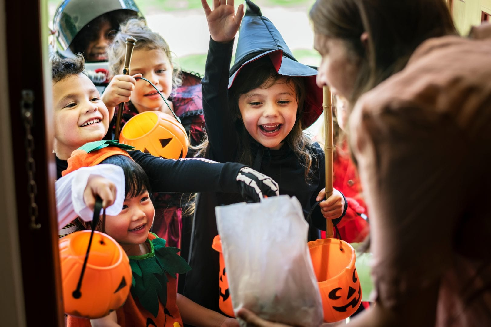 a group of kids in costume holding orange pumpkins. Theyre smiling and laughing as they trick or treat at a woman's front door.