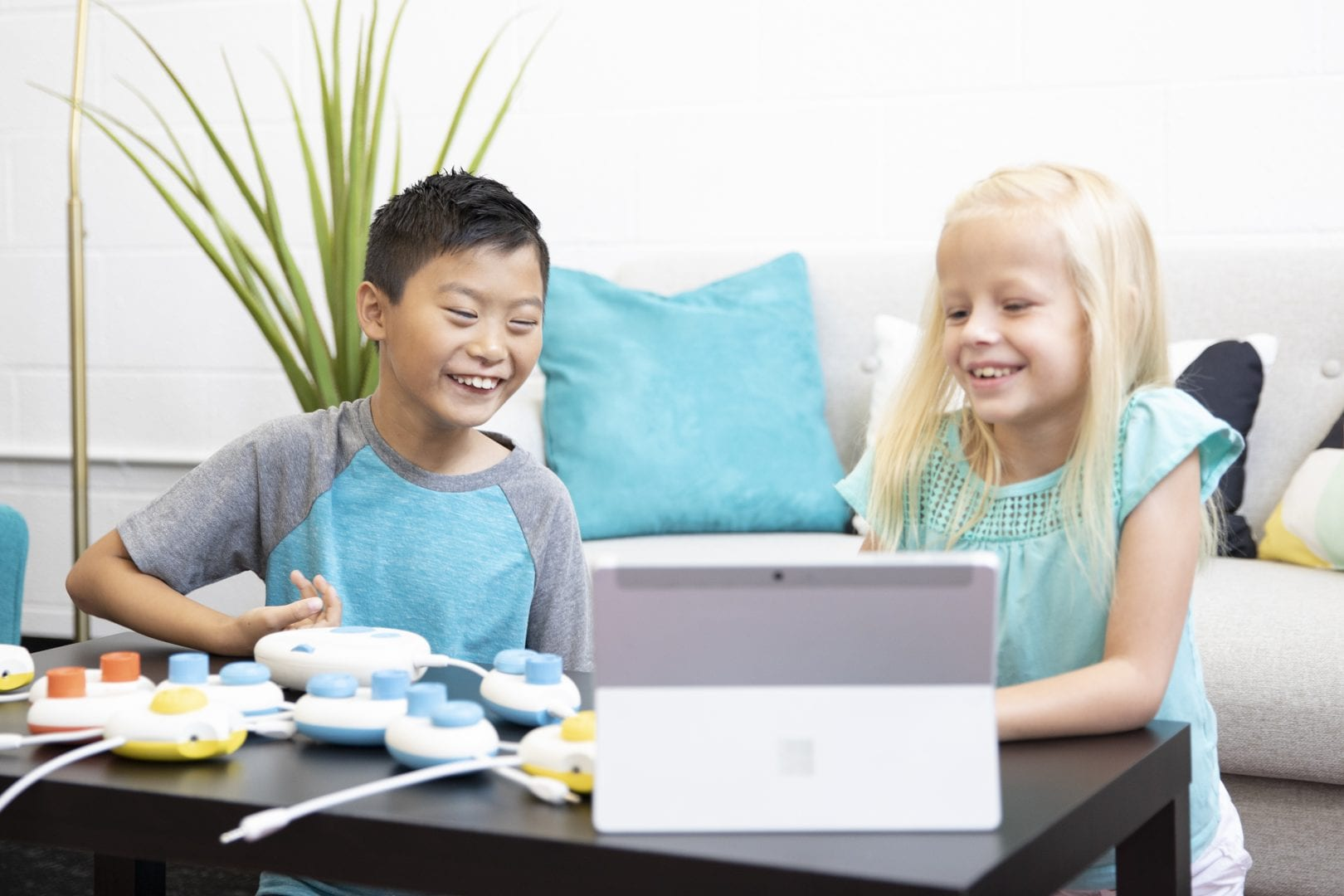 a boy and girl in a living room playing with Code Jumper