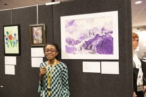 a young artist, smiling and holding her white cane, stands in front of her purple landscape artwork