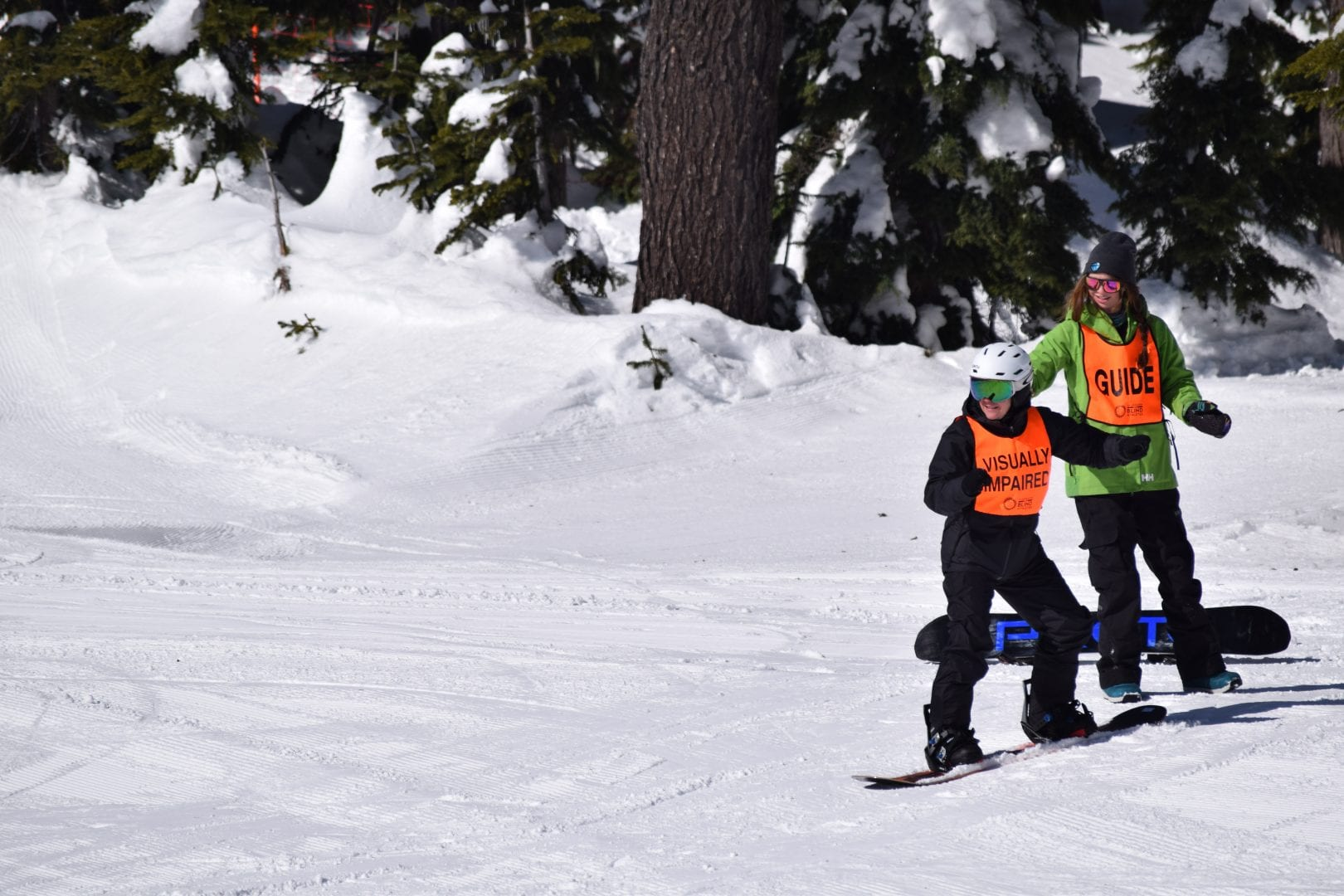 a student snowboarder in an orange vest on the snow, an instructor is behind them