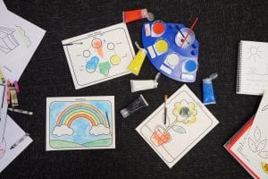 paint pot palette with paint brushes, tubes of paint, and painted pictures on the floor