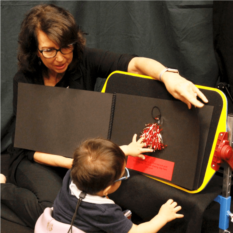 Diane and a child working with a yellow, black, and red CVI appropriate product