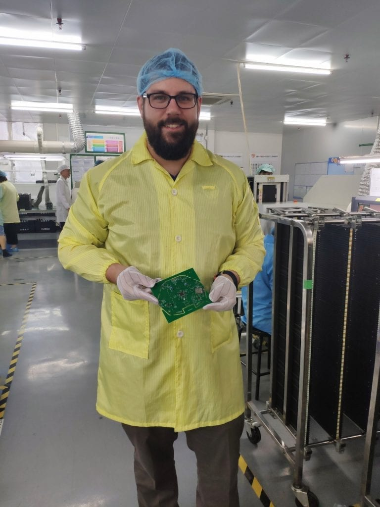 andrew in a labcoat, hair net, and rubber gloves holding a piece of circuit board and smiling