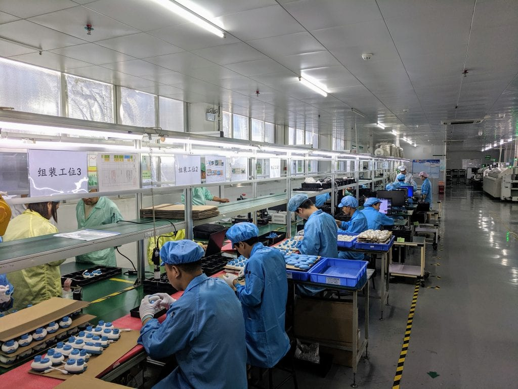 a line of factory workers in blue jackets and hats at stations producing different portions of the Code Jumper kit