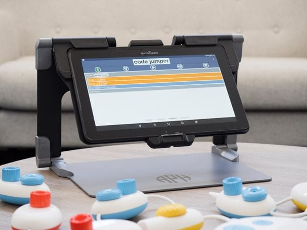Code Jumper's hub and colorful pods are connected to the MATT Connect with the Code Jumper app and a thread of code displayed on the tablet's screen.