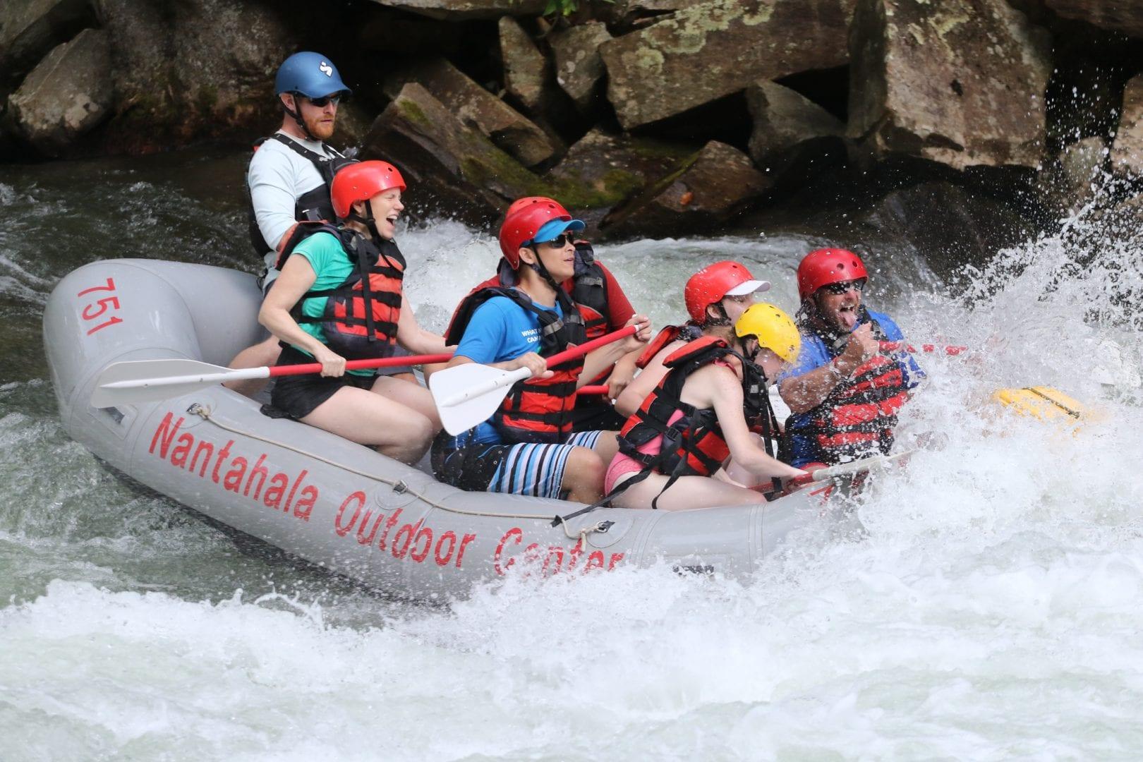 Campers enjoy navigating their raft through white water rapids