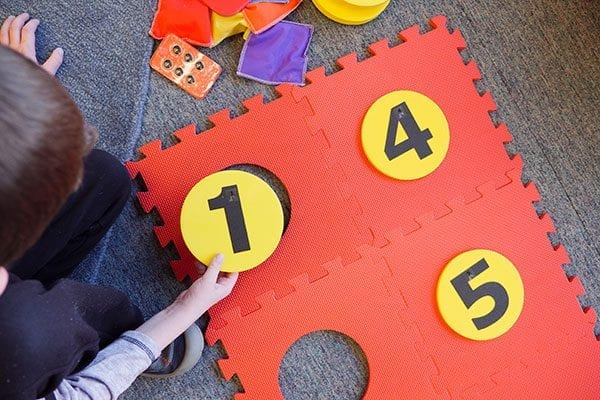 a student placing a foam yellow dot with the number one on it into the red foam floor mat braille cell