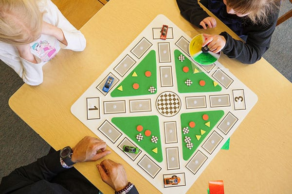 overhead view of two students and an adult sitting around a color raceway board playing the game