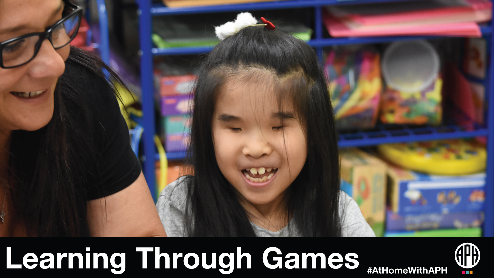 "a young girl smiling and playing with a woman. Text reads ""Learning through games #AtHomeWithAPH"""