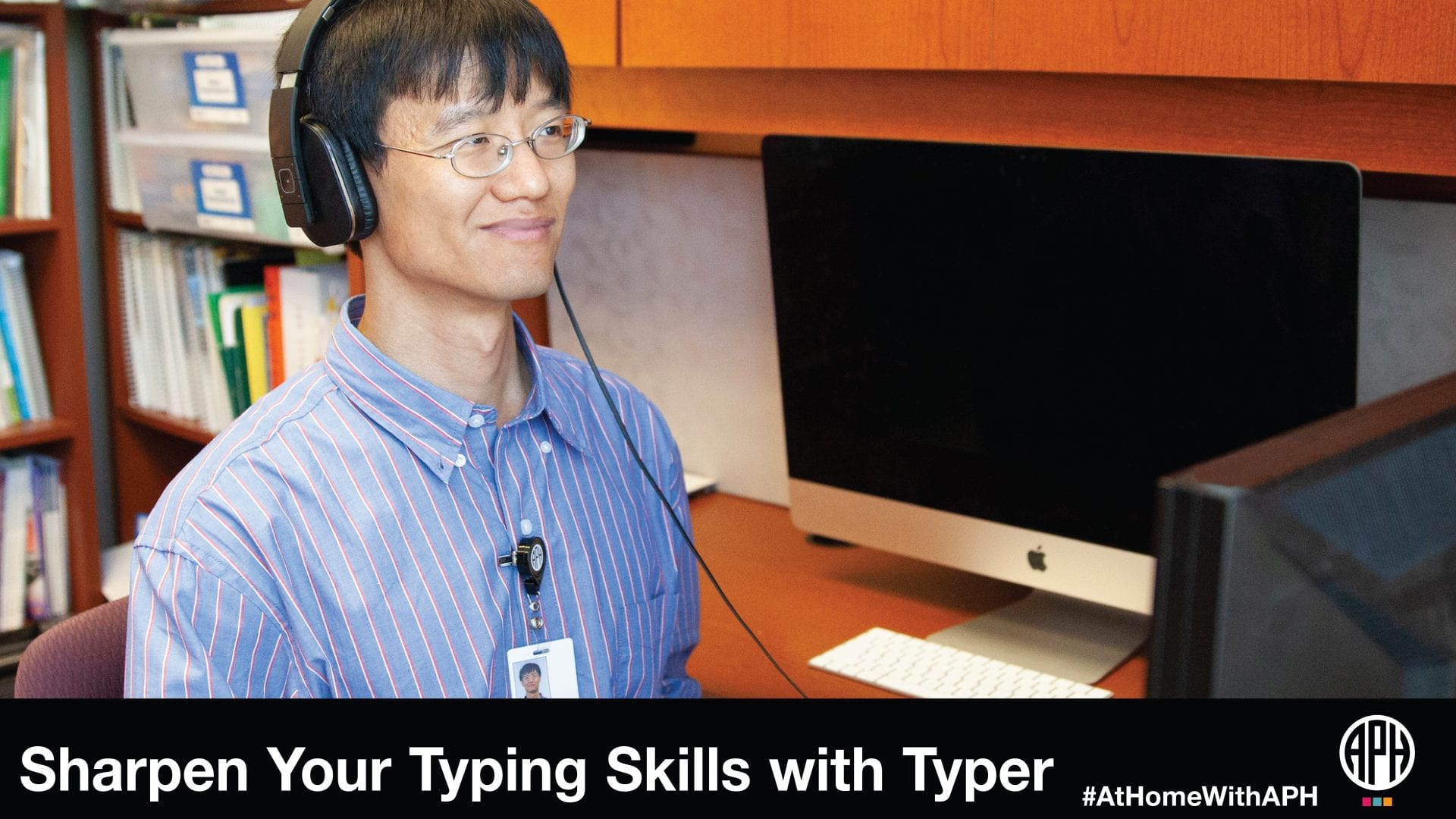 "a man with glasses wearing headphones and sitting at a computer. text reads ""Sharpen your typing skills with typer. #AtHomeWithAPH"" APH logo"