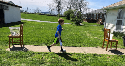 a child running from one chair to the other along the lead line